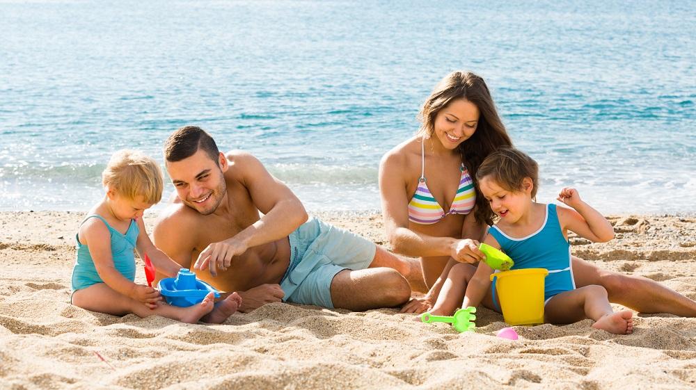 Pais com bebês na praia