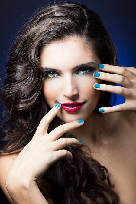 Mulher maquiada e unhas com esmalte