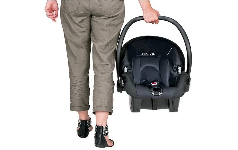 Mulher segurando bebê conforto alça